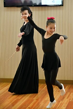 North Korea, Pyongyang - May 2, 2019: Young ballerina in choreography class with her teacher in the Mangyongdae Children's Palace Standard-Bild - 128465011