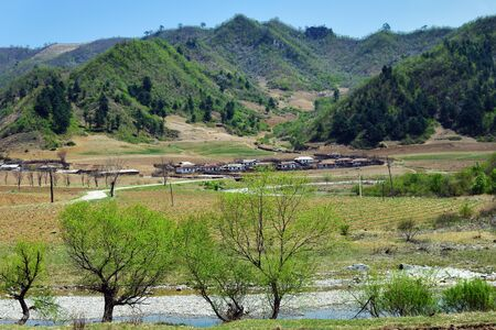 Countryside landscape, North Korea. Village and mountains at background