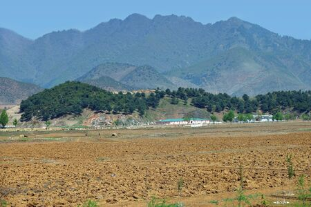 North Korea landscape. Mountains, village and plowed agriculture fields in foreground. Peasants work in the fields 免版税图像