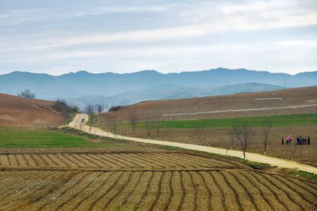 North Korea landscape. Mountains, dirt road and plowed agriculture fields in foreground. Peasants gathering to work in a fields at dawn
