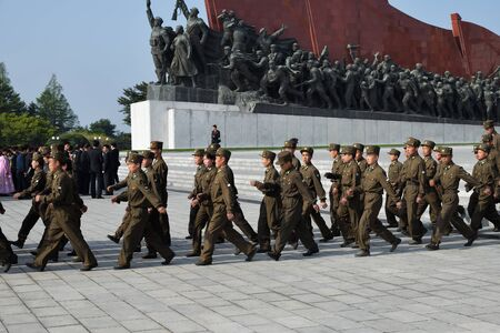 Pyongyang, North Korea - May 1, 2019: A company of soldiers marching along Pyongyang street against the Mansudae monument. Mansu hill