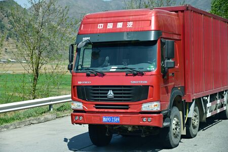 North Korea - May 5, 2019: Road in Countryside. The red heavy truck carrying a container on a mountain road. Editorial