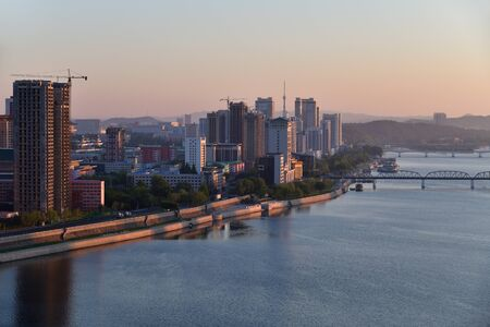 Sunrise in Pyongyang, North Korea and Taedong River in the morning fog. View facing upstream, modern residential complex and new construction site. View from Yanggakdo island