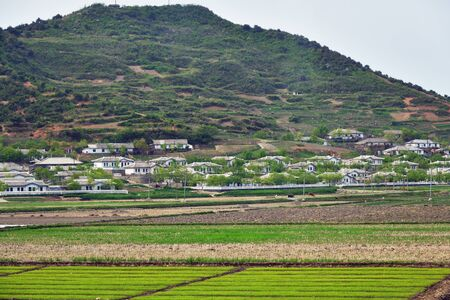 Countryside landscape. Typical houses of peasants built by the state for residents of countryside. North Korea DPRK Village on the mountain slope and green fields
