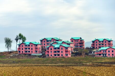Countryside landscape, an agricultural fields and urban village with typical architecture. All housing for householders is provided by the state for free 免版税图像