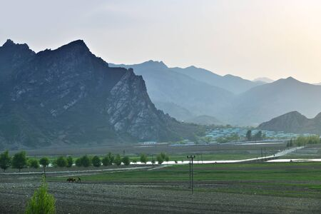 North Korea landscape. Mountains, village and plowed agriculture fields in foreground. Peasants work in the fields at sunset 免版税图像