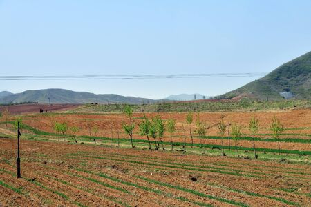 North Korea landscape. Mountains and plowed agriculture fields in foreground. Peasants work in the fields