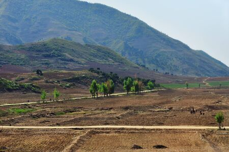 North Korea landscape. Mountains, dirty roads and plowed agriculture fields in foreground. Peasants work in the fields