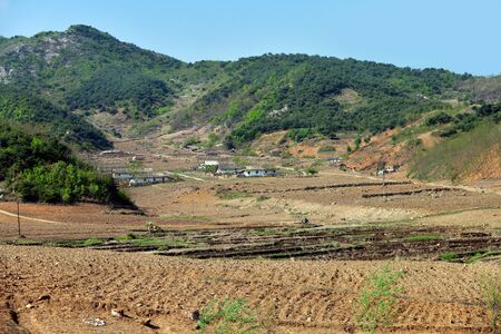 North Korea landscape. Mountains, village and plowed agriculture fields in foreground. Peasants work in the fields 写真素材