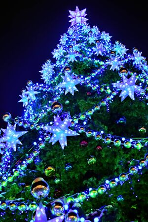 Christmas tree decorated with colorful neon garlands against the night sky outdoor. Christmas and New Year holiday