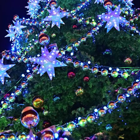 Christmas tree decorated with colorful neon garlands. Christmas and New Year holiday