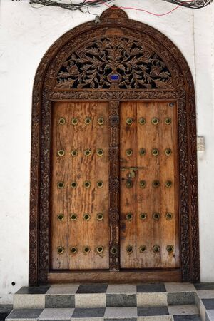 Ancient traditional wooden carved door with ornaments and bronze spike in Stone Town, Zanzibar,Tanzania, East Africa