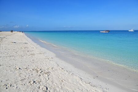 White sandy beach and boats on a coast in Kendwa resort shown at morning, Zanzibar, Tanzania, Africa
