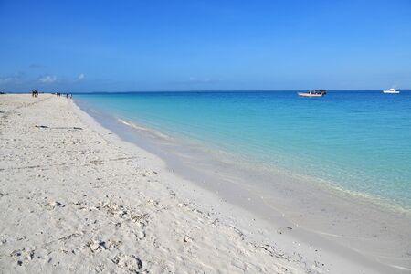 White sandy beach and boats on a coast in Kendwa resort shown at morning, Zanzibar, Tanzania, Africa