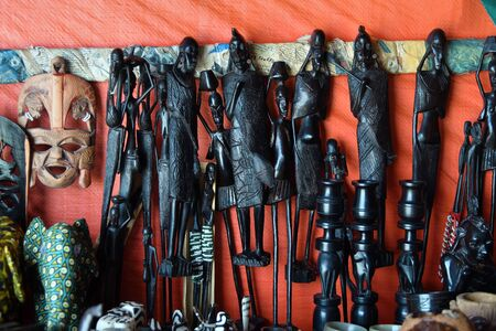 Handcrafted or handmade african souvenir. Traditional african primitive figurine in Makonde style and others souvenirs sold in a market stall. Kendwa, Zanzibar, Tanzania, Africa