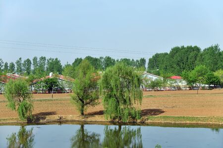 Countryside landscape, North Korea. Village, cultivated agricultural fields and water pond on foreground