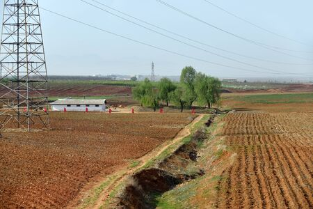 Countryside landscape, North Korea. Cultivated agricultural fields and electric power line mast 写真素材