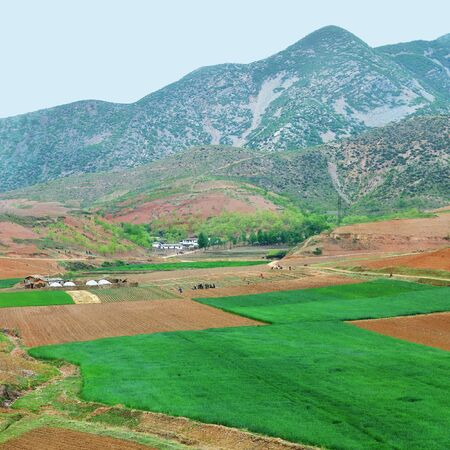 Countryside landscape, North Korea. Cultivated agricultural fields, village and mountains at background not far from Kaesong shown at dawn