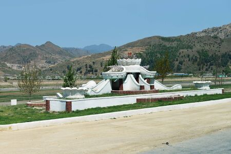 North Korea. Flower bed decoration along a local road, mountains landscape in background
