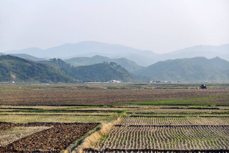 Countryside landscape, North Korea. Cultivated agricultural field and mountain at background during sunset time 写真素材