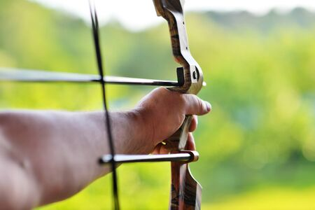 Man's hand over blur background of Archery with a bow in the foreground during an archery competition. Selective focus