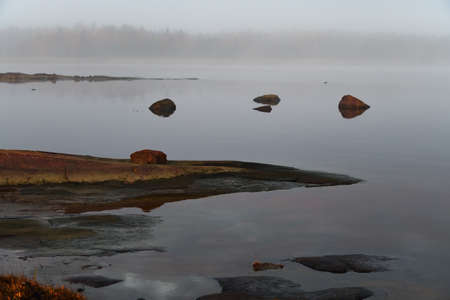 Beautiful landscape of the shore of the White Sea at sunrise. Onega Gulf, Karelia, Russia. The littoral zone at high tide