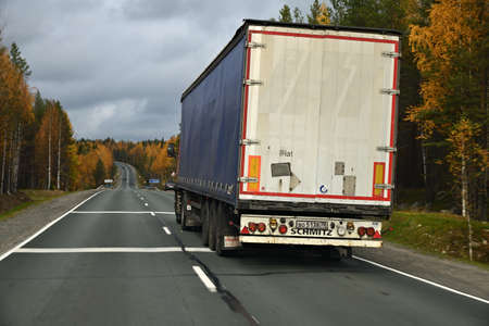 Karelia, Russia - September 30, 2020: Truck goes along the highway through the autumn forest, trucking long distances