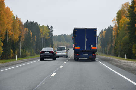 Karelia, Russia - September 30, 2020: Truck and other cars go along the highway through the autumn forest. Kola road. Overtaking maneuver