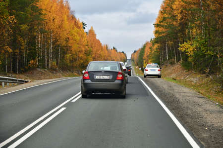 Karelia, Russia - September 30, 2020: Cars go along the highway Kola through the autumn forest