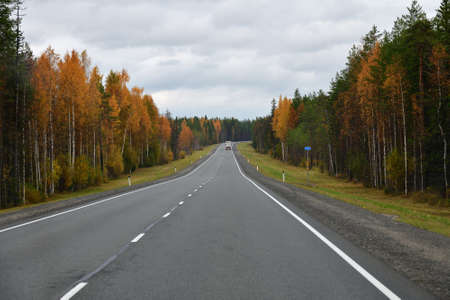 Karelia, Russia. Truck goes along the highway through the autumn forest. Kola road. Overtaking maneuver Imagens