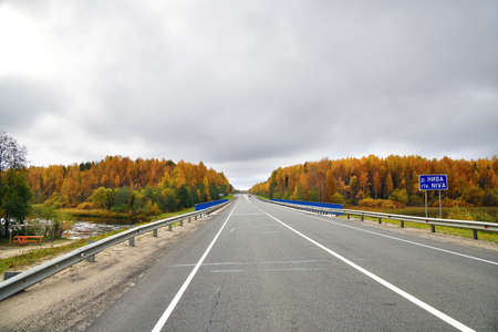 Karelia, Russia. The highway Kola through the autumn forest. Bridge accros niva river