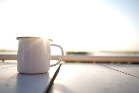 Stock Photo - Cup of tea on white wooden blurred sunset on river