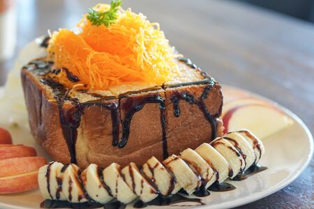 Honey toast toping golden egg strips with chocolate syrup and banana apple
