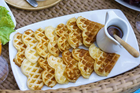 Plate with delicious waffle honey. On a ratten deck background. View from above.