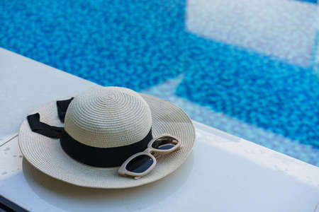 Hat and sunglasses at the side of swimming pool, summer travel concept.