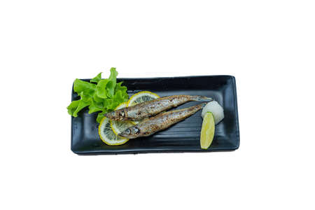 Japanese Food : Grilled Shishamo Fish on Black dish with Lemon on White Background Stock Photo