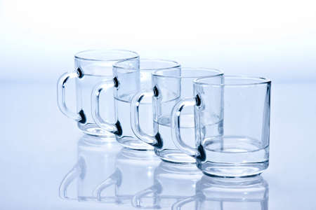 unevenly: four blue cups filled with water unevenly