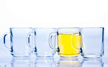 differentiate: four glass cups three of which are empty and one with a yellow tea