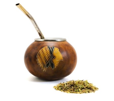 Cup from calabash and straw with dry mate on pure white background