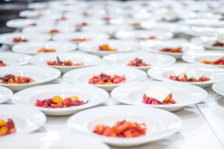 Many plates dish of tomatoe red salad being prepared in a comercial indistrial professional kitchen galley for and event party