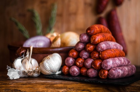 Still life photo of white and red spicy sausages in triangle piramid next to garlic in a traditional kitchen onion isolated