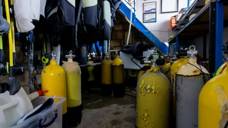 Scuba diving gear storage with many oxygen yellow tanks in an old store
