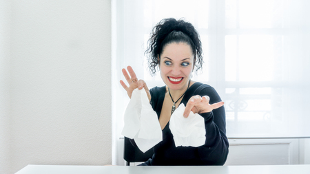 Portrait of normal woman sick with allergies or flu looking at tissues with disgusted face expression. Blue eyes, black hair, white skin, red lips. blank copy space