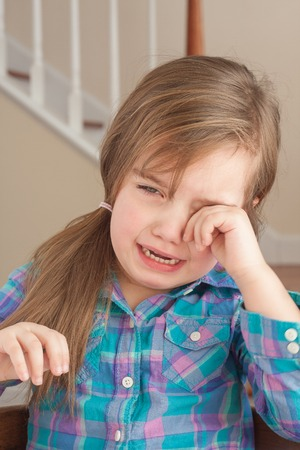 sad adorable little girl crying at home photo