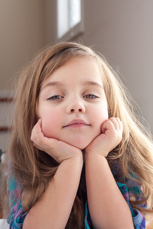 face centered: little girl with hands up her chin. Stock Photo