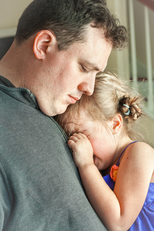 goodbye: sad father comforting his crying preschool age daughter. Great parenting image