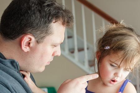 spoken: Preschool age little girl getting spoken to by her father. preschool age little girl getting spoken to by her father. Stock Photo