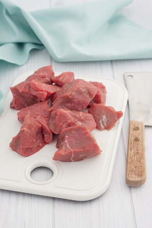 non vegetarian: chunks of raw beef on a white cutting board Stock Photo