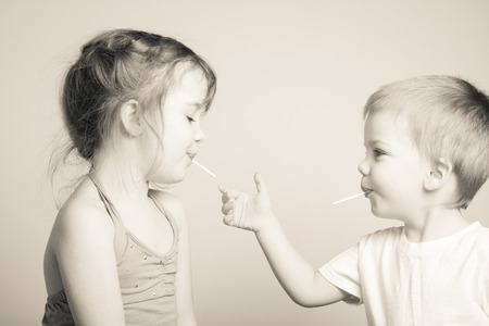 black and white photo of siblings playing with each others lollipops Imagens