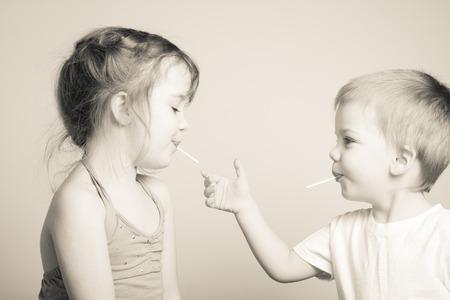 zwart-wit foto van de broers en zussen spelen met elkaars lolly Stockfoto